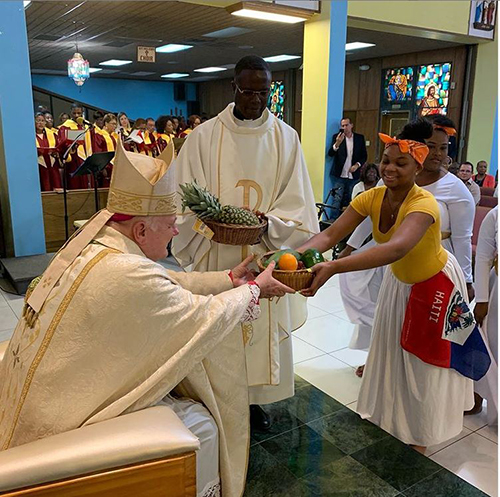 Archbishop Thomas Wenski receives the offertory gifts during Mass at St. Helen Parish in Lauderdale Lakes Aug. 18. He celebrated a special trilingual Mass for the feast day of St. Helen. Looking on is Father Lucien Pierre, St. Helen's pastor.