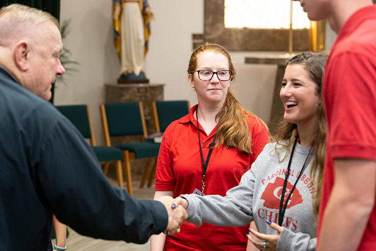 Archbishop Thomas Wenski greets Cardinal Gibbons High School student representatives after arriving on campus Aug. 22 to celebrate Mass for the opening of the school year.
