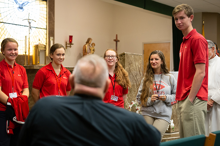 Archbishop Thomas Wenski chats with Cardinal Gibbons High School student representatives before celebrating Mass Aug. 22 for the opening of the school year.
