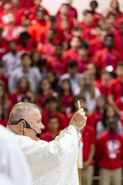 Archbishop Thomas Wenski elevates the consecrated host while celebrating Mass for the opening of the school year at Cardinal Gibbons High School Aug. 22, feast of the Queenship of Mary.