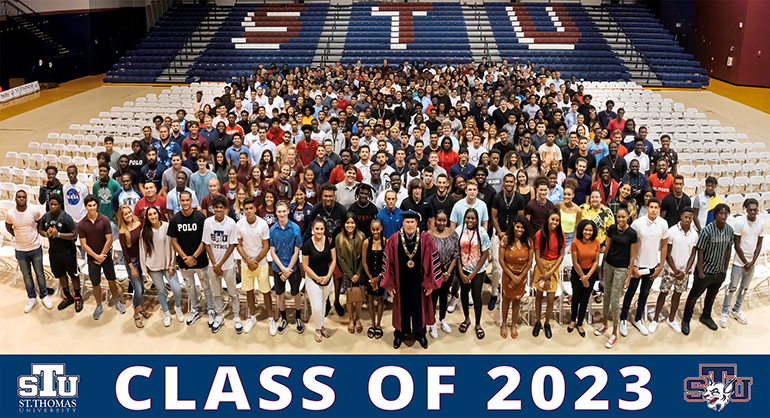 St. Thomas University President David Armstrong, center front, poses with members of the incoming freshman class after their induction ceremony Aug. 23. Due to the unprecedented size of this incoming class - 677 new undergraduate students, more than double last year's enrollment, including 555 freshmen - the formal ceremony was moved to the university's athletic center.