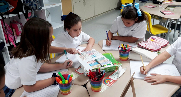 Students at St. Agnes School learn about Spanish by studying various designs of Hispanic currency.