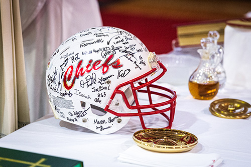 After celebrating a Mass for the opening of the school year on Aug. 22 at Cardinal Gibbons High School in Fort Lauderdale, Archbishop Thomas Wenski received a special gift from members of the school's football team, who signed a helmet for the archbishop. Area priests were also given guest passes to upcoming football games.