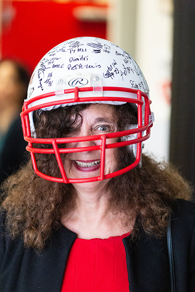 Kim Pryzbylski, superintendent of Schools for the Archdiocese of Miami, sports a special gift from members of the Cardinal Gibbons High School football team in Fort Lauderdale Aug. 22. The teammates signed a gift football helmet for the  Archbishop Thomas Wenski while area priests were given guest passes to upcoming football games.