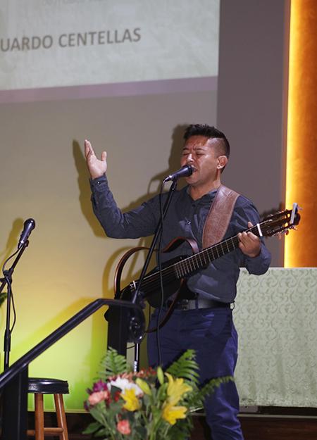 """Eduardo Centellas, cantautor boliviano, canta """"La sangre de Cristo"""" durante los Premios David, en la parroquia Corpus Christi. Centellas es director de música de la misión San Francisco y Santa Clara de la misma iglesia. Dijo que empezó a cantar música católica hace 15 años y sus composiciones se enfocan en la Eucaristía."""