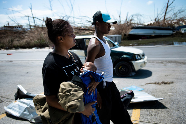 Isabel Strachan, left, walks with her son Nathiel Strachan and brother-in-law Kyreem Jonassaind after Hurricane Dorian Sept. 5, 2019, in Marsh Harbor, Great Abaco. Hurricane Dorian lashed the Carolinas with driving rain and fierce winds as it neared the US east coast Thursday after devastating the Bahamas and killing at least 20 people.