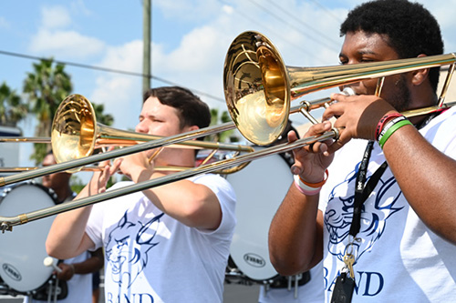 Members of St. Thomas University's marching band play at the school's first game.