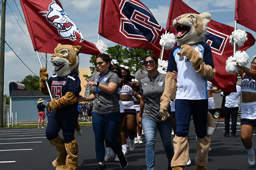 St. Thomas University's mascots, flagbearers and cheerleaders run into the field before the first football game Sept. 7.