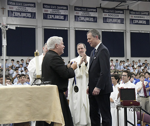 Brother Patrick McNamara, USA Provincial of the Marist Brothers, presents Thomas G. Kruczek with a specially-created medal during Kruczek's installation as Christopher Columbus High School's second president. Looking on is school alumnus Father Alejandro Rodriguez Artola.