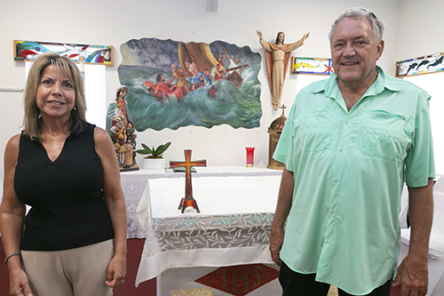 Nancy McCrosson, bookkeeper and property manager at St. Peter, poses with Knights of Columbus John Krieger in front of the altar salvaged from the chapel of the church. Behind them is a replica of the painting that adorned the church's sanctuary.