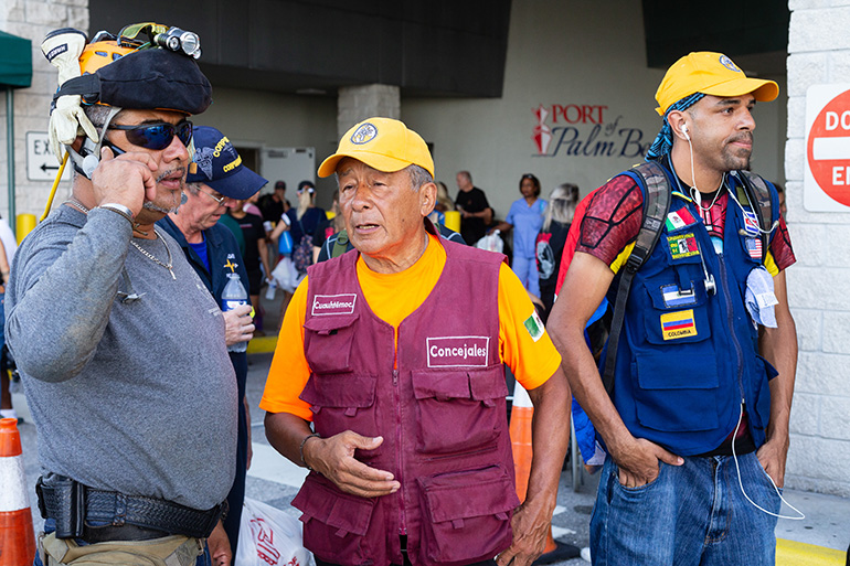 Hector Mendez of Mexico City, center, speaks to a fellow search-and-rescue volunteer after arriving at the Port of Palm Beach Sept. 18. He was among the first responders and search-and-rescue volunteers and professionals from the U.S. and Latin America who embarked on a mission in the northern Bahamas in response to the category 5 Hurricane Dorian, which slammed into the islands Sept. 1-3, causing historic devastation. The Florida-based Bahamas Paradise Cruise Line concluded its second humanitarian round trip mission by providing the transportation from Florida to Freeport, Grand Bahama, carrying some 400 volunteers and 200 visa-carrying Bahamas evacuees.