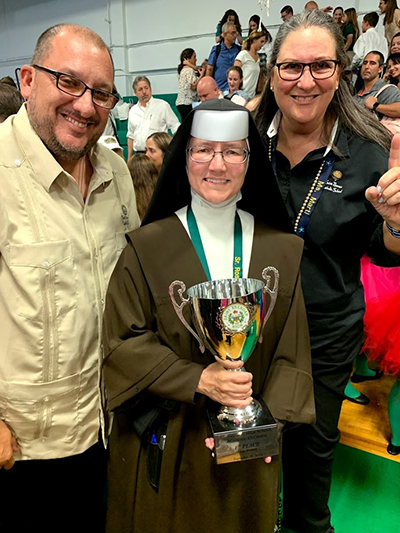 St. Theresa School faculty pose with the winning trophy for first place overall in the large school division of St. Brendan High's Academic Olympics, from left: Daniel Serrano, seventh and eighth grade teacher, Carmelite Sister Rosalie Nagy, principal, and Gloria Marti, vice principal.