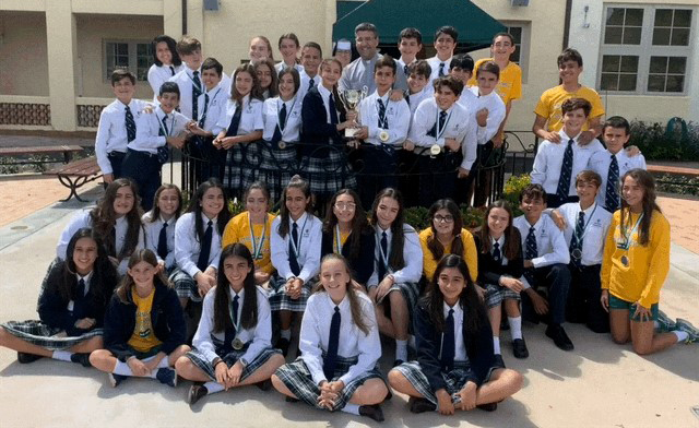 St. Theresa School students who participated in the St. Brendan High Academic Olympics, winning First Place Overall in Large Division Schools, pose with Carmelite Sister Rosalie Nagy, principal, and Father Manny Alvarez, pastor.