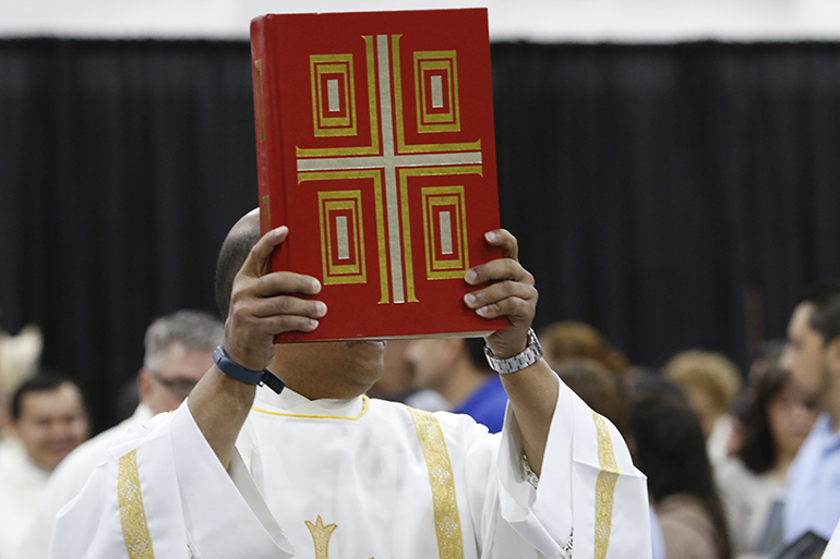 "Pope Francis, in proclaiming the Sunday of the Word of God, suggested parishes should highlight the ""proclamation of the word of the Lord and emphasize in the homily the honor that it is due."" In this file photo, Deacon Pierre Douyon of St. Maximilian Kolbe Parish in Pembroke Pines carries the Book of the Gospels during Mass."