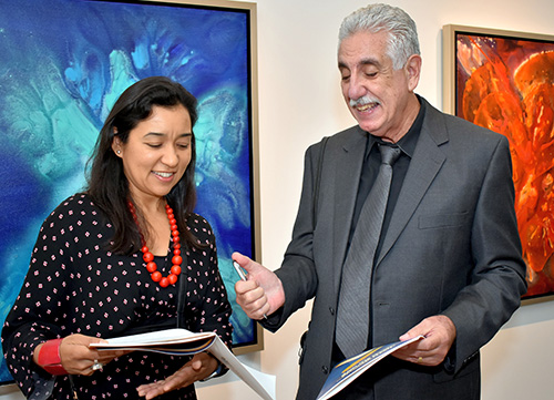 Emilio Hector Rodriguez autographs a program book for art blogger Dainy Tapia during the opening of his exhibit at St. Thomas University. The show,