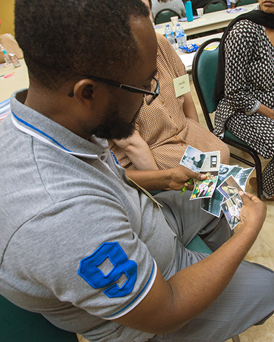 Chavannes Metayer, from Share Your Heart, looks over photos given to participants in the bereavement ministry training, and chooses a photo which is meaningful to him during the bereavement ministry training day held at St. Agnes Church, Key Biscayne, Sept. 14.