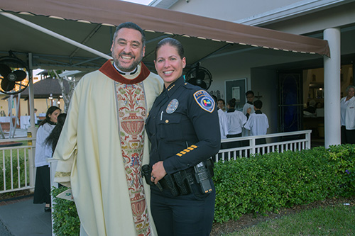 Father Robert Ayala, St. Matthew pastor and one of three Hallandale Beach police chaplains, poses for a photo with Hallandale Beach Police Chief Sonia Quinones, before the parish's 60th anniversary Mass.