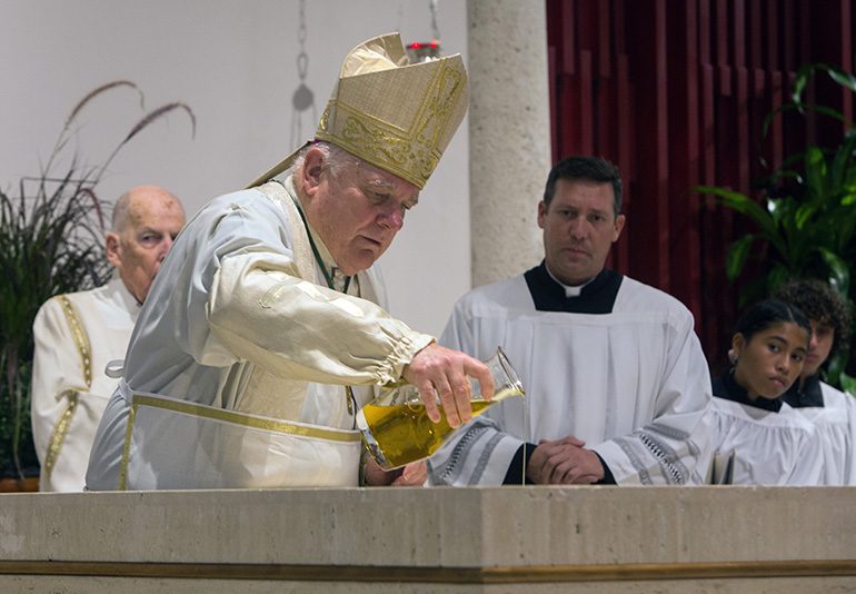 Archbishop Thomas Wenski pours oil of chrism on St. Matthew Church's new altar as he consecrates it during the parish's 60th anniversary Mass, Sept. 25, 2019.