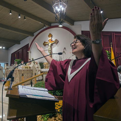 Choir member Meredith Schuster leads the congregation in song during the 60th anniversary Mass for St. Matthew Parish, Sept. 25, 2019.