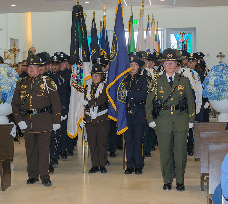 Police honor guards from various departments enter Our Lady of Guadalupe Church in Doral for the Blue Mass Sept. 27. Archbishop Thomas Wenski celebrated the Mass for the feast day of St. Michael the Archangel, patron saint of law enforcement officers.