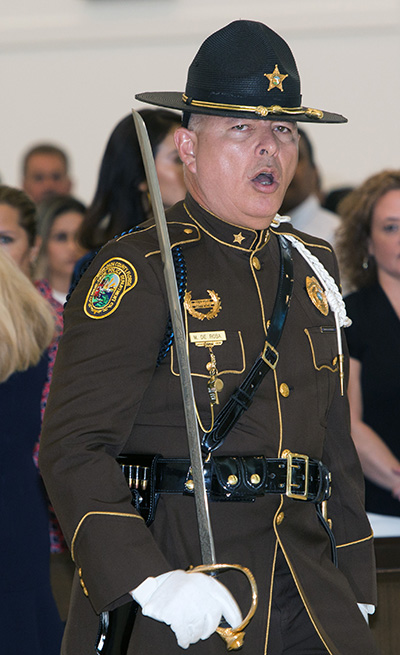 Miami Dade Police Officer Marcos DeRosa, an honor guard member, calls out orders to fellow officers carrying the flags of their various police departments as they process into Our Lady of Guadalupe Church for the Blue Mass.