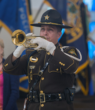 Miami Dade police officer Eduardo Gaitan, an honor guard member, plays the trumpet before the start of the Blue Mass at Our Lady of Guadalupe Church in Doral.