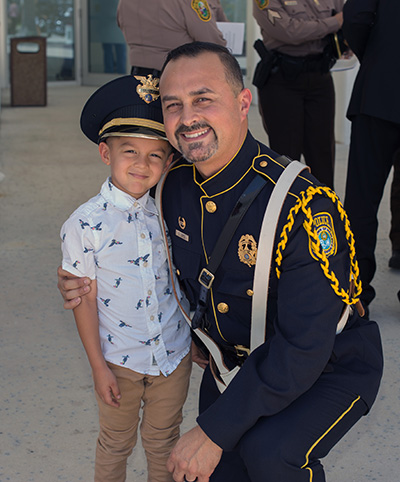 Jeronimo Lopez, 4, poses for a photo with his father, Cristian Lopez, a Medley police officer and police honor guard member, after the celebration of the Blue Mass.
