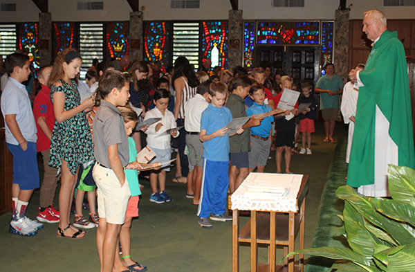 Msgr. Vincent Kelly calls the children of the parish to the altar as he celebrates the family Mass Aug. 25. The children are all enrolled in religious education, an important ministry of the parish that has continued to grow over the past 50 years. Religious education programs are part of the parish's mission to spread and pass along the faith to the generations.