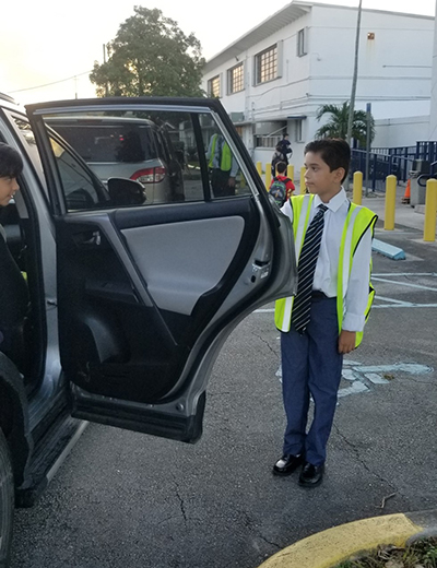 Diego Martinez, a fifth-grader at Blessed Trinity School in Miami Springs, takes his principal-for-a-day job seriously, beginning by welcoming parents, students and faculty as they arrive at the car line early in the morning.