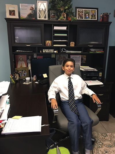 Diego Martinez, a fifth-grader at Blessed Trinity School in Miami Springs, sits in the principal's chair Oct. 2, doing his job as principal for a day. His parents literally