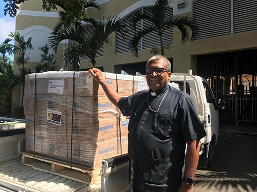Nassau Archbishop Patrick Pinder stands by the first of two shipments of relief supplies sent by Catholic Charities of the Archdiocese of Miami to aid those recovering from Hurricane Dorian in The Bahamas. Peter Routsis-Arroyo, CEO of Catholic Charities, said,