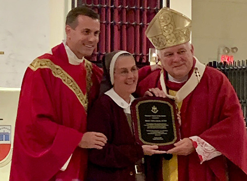 "Archbishop Thomas Wenski and Msgr. David Toups, left, rector of St. Vincent de Paul Regional Seminary in Boynton Beach, recognize Mother Adela Galindo, founder of a new religious community, the Servants of the Pierced Hearts of Jesus and Mary, just before the Friends of the Seminary annual dinner Oct. 18, 2019. ""The community continues to grow and flourish even beyond the Archdiocese of Miami,"" Archbishop Wenski said."