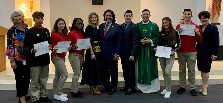 The five recipients of this year's Jorge Luis Lopez Esq. Scholarship at Msgr. Edward Pace High School pose with Jorge Luis Lopez, his wife and one of their sons (center), Pace Principal Ana Garcia (far left), Father Richard Vigoa, and Celia Rouco, director of Development at Pace.