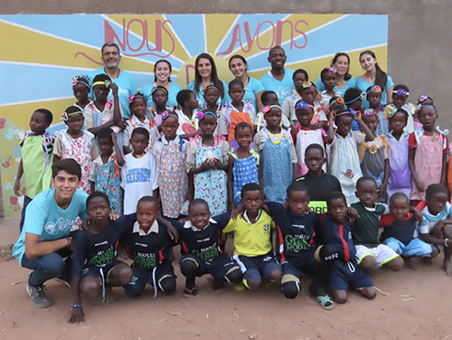 Hope for Kasai missionaries from South Florida pose with children from the village of Mpiana Nita in front of the mural painted by Our Lady of Lourdes Academy student Emma Uddenberg. It reads,