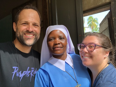 Andres Novela and another missionary from Amor en Accion pose with a sister from Haiti during a mission trip to the island nation.