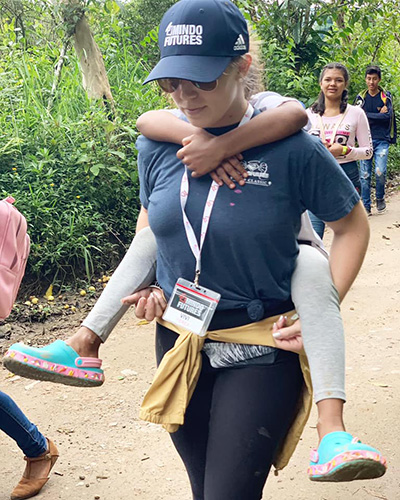 Some piggy-back fun: Mindo Futures missionary Viviana Yerex carries a friend during a mission trip in Mindo, Ecuador.