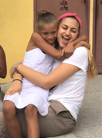 Amor en Accion missionary Lucia Pannunzio gets a big hug from a new friend she made during a mission trip in the Dominican Republic this summer.