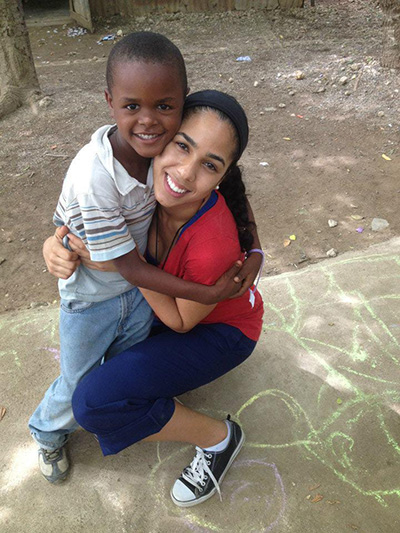 Amor en Accion missionary Janelle Jay gets a big hug from a new friend during a mission trip to the Dominican Republic.