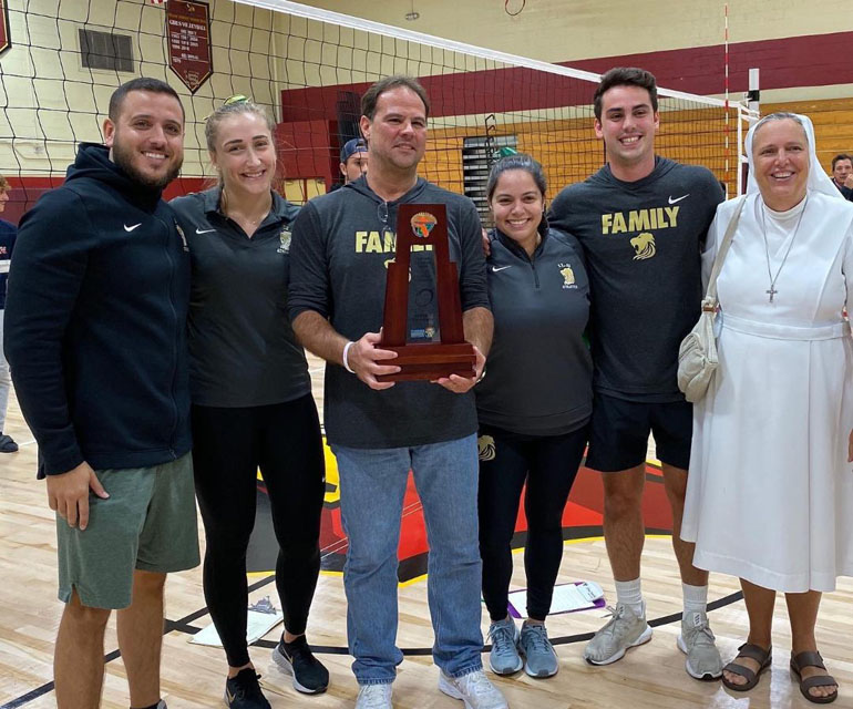 Immaculata La Salle girls volleyball coaches, trainers, supporters and Principal Sister Kim Keraitis, FMA, pose with their trophy after the Lady Royals won the 2019 Girls Volleyball District Championship in 4A District 15 on October 17 against MAST Academy.