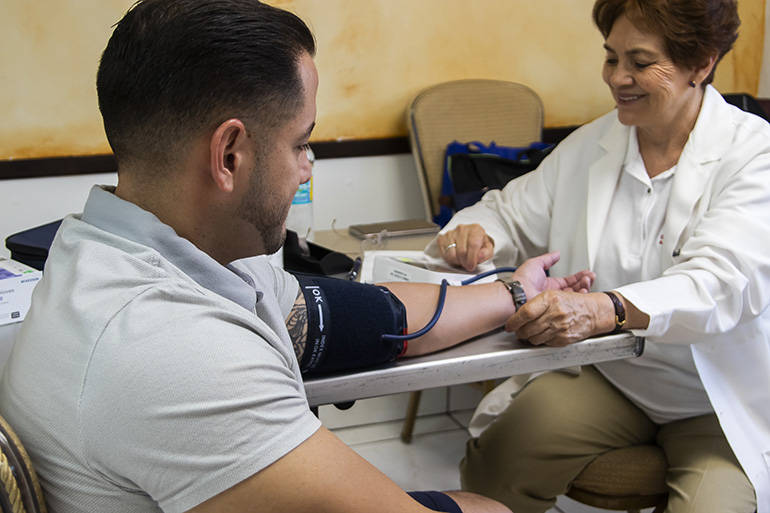 Dr. Gladys Lopez was one of several doctors and medical personnel who volunteered at the free Health Fair at Our Lady of Charity National Shrine Nov. 2. Dr. Lopez began each screening by checking each patient's blood pressure.