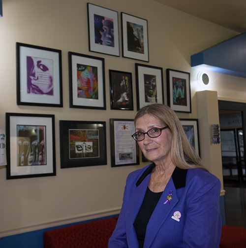 Susan Buzzi, victims advocate, educator, and retired police officer poses with her photographs after giving a talk at St. Thomas University on domestic abuse, Oct. 17, 2019.