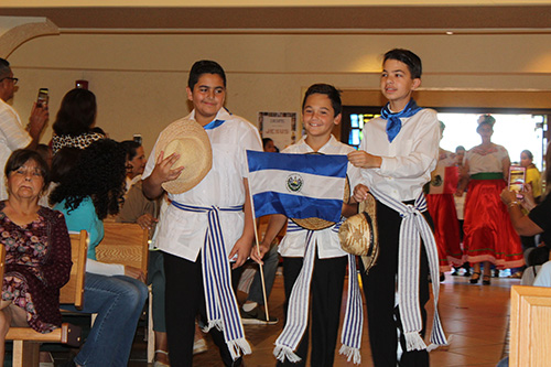 St. Kevin School students bearing the flag of El Salvador process into St. Kevin Church for the Hispanic heritage Mass.