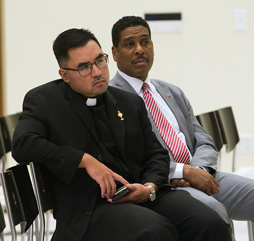 Father Philip Tran, Catholic Campus Ministry chaplain at the University of Miami, and Patrick Stewart, UM's executive director of Development, College of Arts and Sciences, listen to Archbishop Thomas Wenski speak at the UM forum on