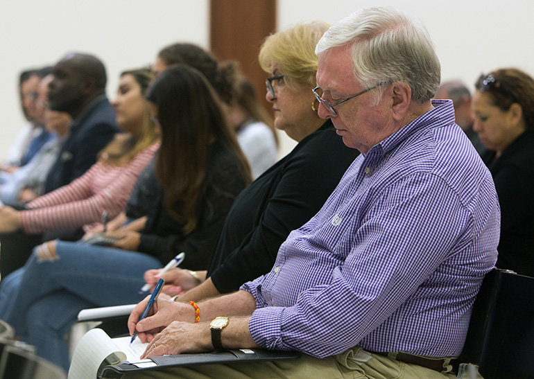Peter England and Julie Romero, of St. Louis Church in Pinecrest, take notes during Archbishop Thomas Wenski's talk at a University of Miami forum on
