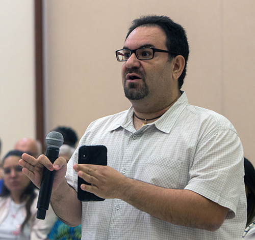 Louis Hernandez, a University of Miami alum, asks what the Catholic Church can do to unify Catholics on various political issues during a question and answer session following Archbishop Thomas Wenski's talk at a UM forum on