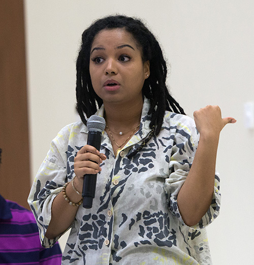 Rae Williams, a University of Miami political science major and vice president of UM's Amnesty International chapter, asks about Catholic Legal Services during the question and answer session that followed Archbishop Thomas Wenski's talk at a UM forum on