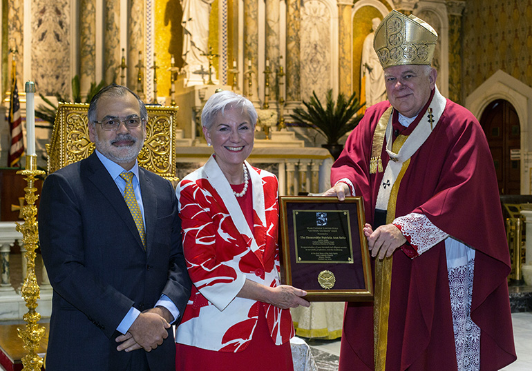 Raoul Cantero, last year's Lex Christi, Lex Amoris Award recipient, poses for a photo after presenting the 2019 award to Senior U.S. District Judge Patricia Seitz. With them is Archbishop Thomas Wenski, who celebrated the annual Red Mass of the Holy Spirit for the Miami Catholic Lawyers Guild Oct. 24, 2019 at Gesu Church, Miami.
