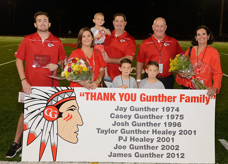 The Gunther family poses together with their commemorative plaque following the halftime recognition ceremony. Back row, from left: James Gunther, PJ Healey, Reece Healey (child being held), Jay Gunther, Terry Gunther. Front row, from left: Taylor Gunther Healey, Peyton Healey, Graeme Healey.