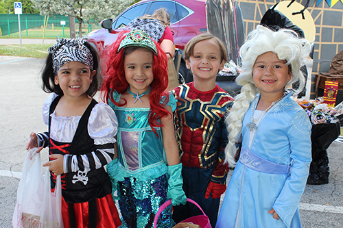 Students from St. Michael the Archangel School dressed as a pirate, Ariel from The Little Mermaid, Spiderman, and Elsa from Frozen are all smiles as they begin trick or treating at the school's third annual trunk or treat event Oct. 31.
