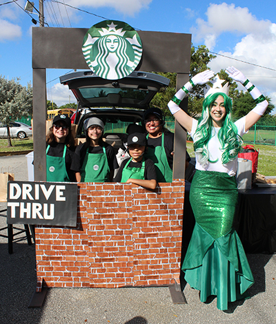 Serving up caramel macchiatos: Student baristas at a Starbucks drive-thru-themed vehicle handed out baked goods, candy, and even a few coffee beverages to adults during this year's trunk or treat at St. Michael the Archangel School. The Starbucks mermaid also greeted visitors.